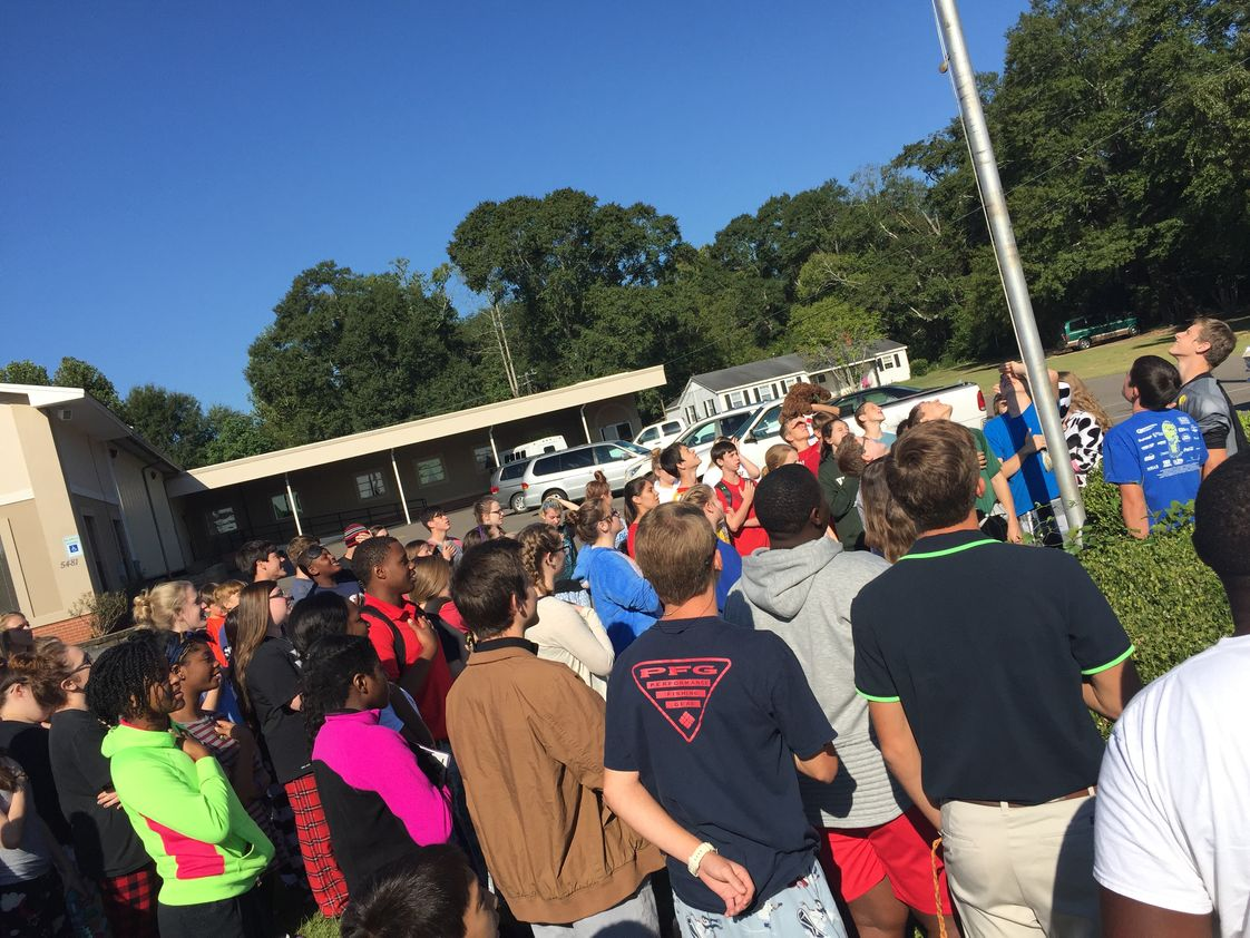 Victory Baptist School Photo - Students gather around the flag pole to pray for our country.