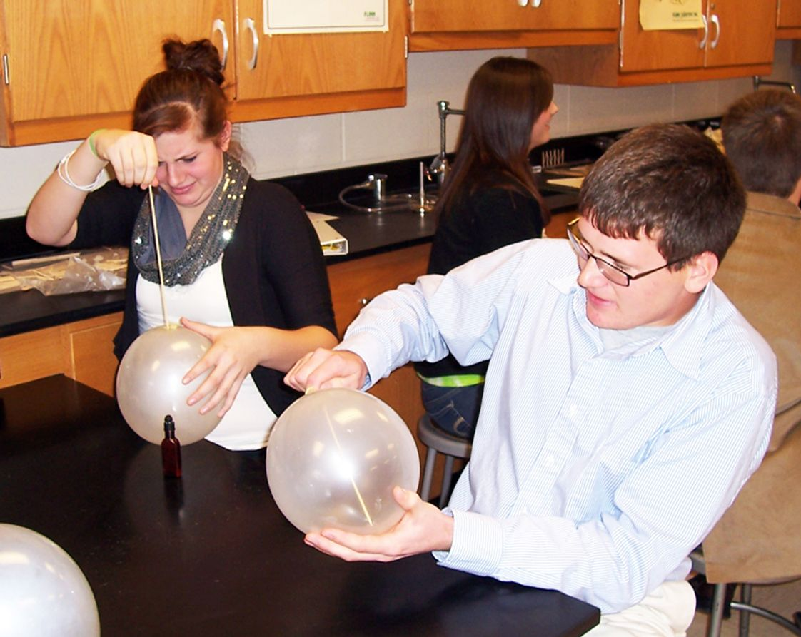 Valley Lutheran High School Photo - Students experiment with polymers as they poke a wooden skewer into a balloon.
