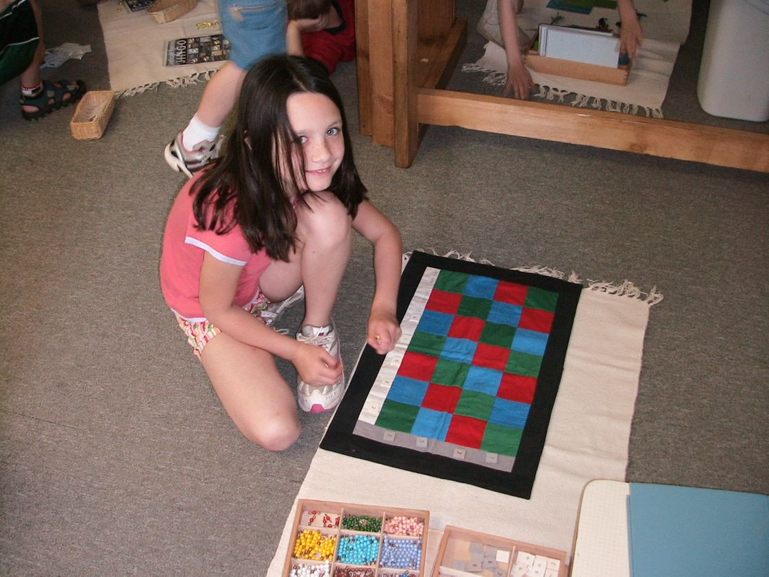 Pinewoods Montessori School Photo - An elementary student doing her math work using Montessori materials. The Montessori math curriculum includes using concrete methods of learning abstract concepts.
