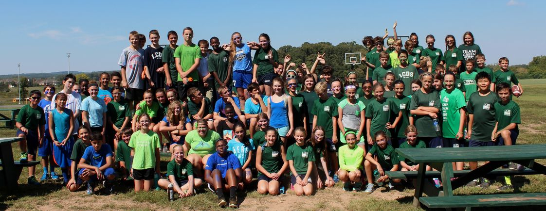 Loudoun Country Day School Photo - Middle school students participate in the traditional Blue and Green Games in September after bonding in a week of activities, including using zip lines, rock climbing, and river rafting. The middle school is divided between blue and green teams throughout the year. Here they pose together after a day of outside activities.