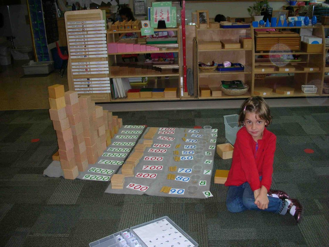 The Sammamish Montessori School Photo #1 - Students delve into a variety of hands-on math work that help them to solidly grasp the concept of quantity and math equations. In this case a kindergarten student has completed the Birds Eye View math work quantifying golden beads from one to 9,999.