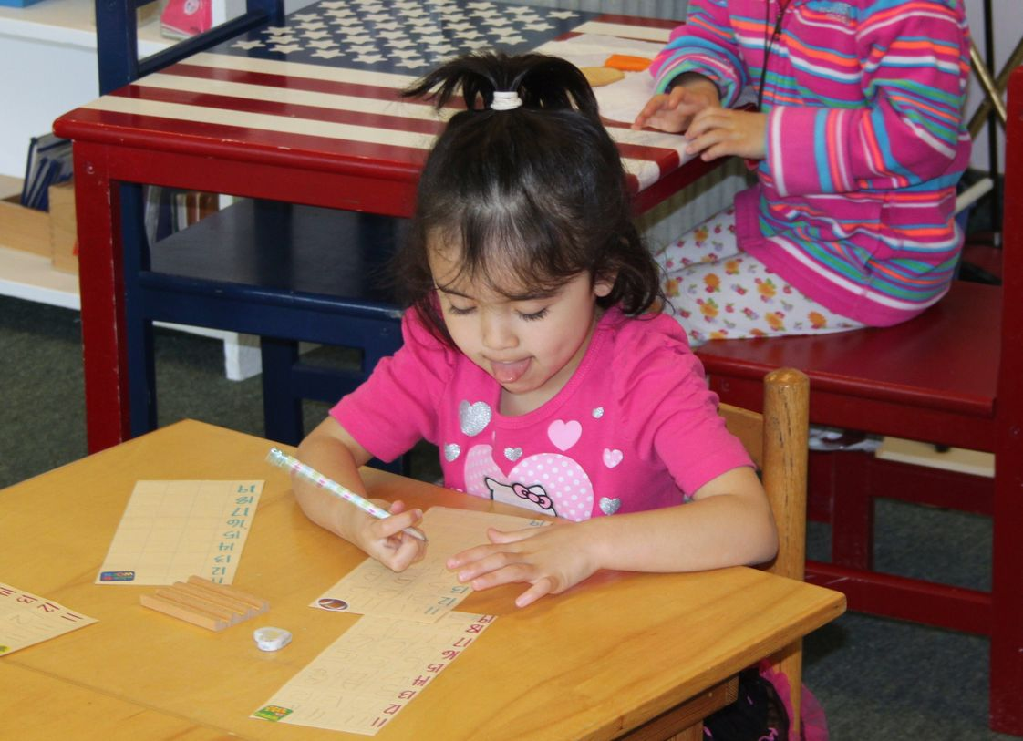 The Happy Childrens Montessori Photo #1 - This girl is concentrating hard on her number papers. She is 4.