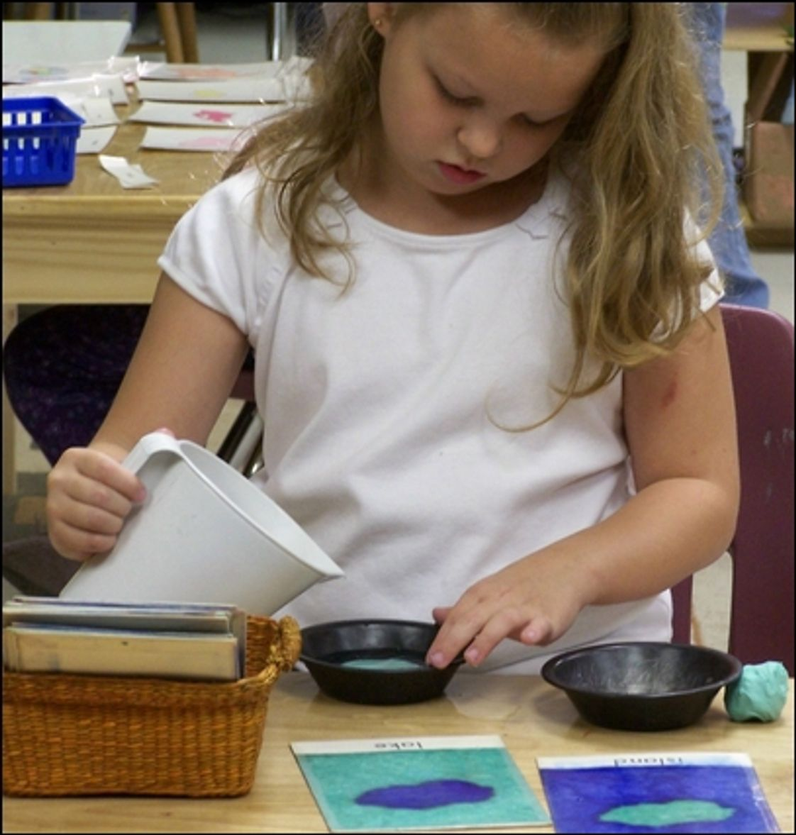 Arkansas River Valley Montessori Photo - An Early Elementary student learns about land forms by creating them with clay and water.