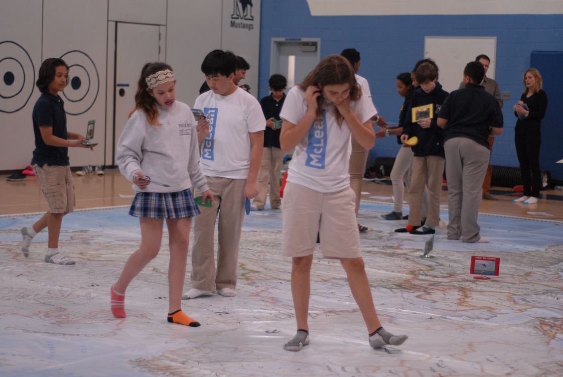 McLean School Photo - Middle School students play learning games and explore the giant National Geographic map on Asia.