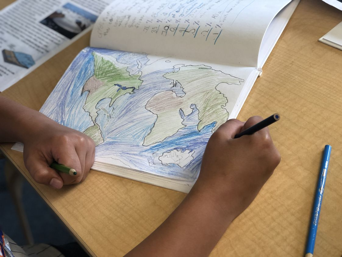 Peconic Community School Photo - PCS students engage in a project-based unity of study each trimester that provides the basis for an integrated, immersive and emergent curriculum. Here, a 5th grade student adds detail to drawing during a unit on glaciers.