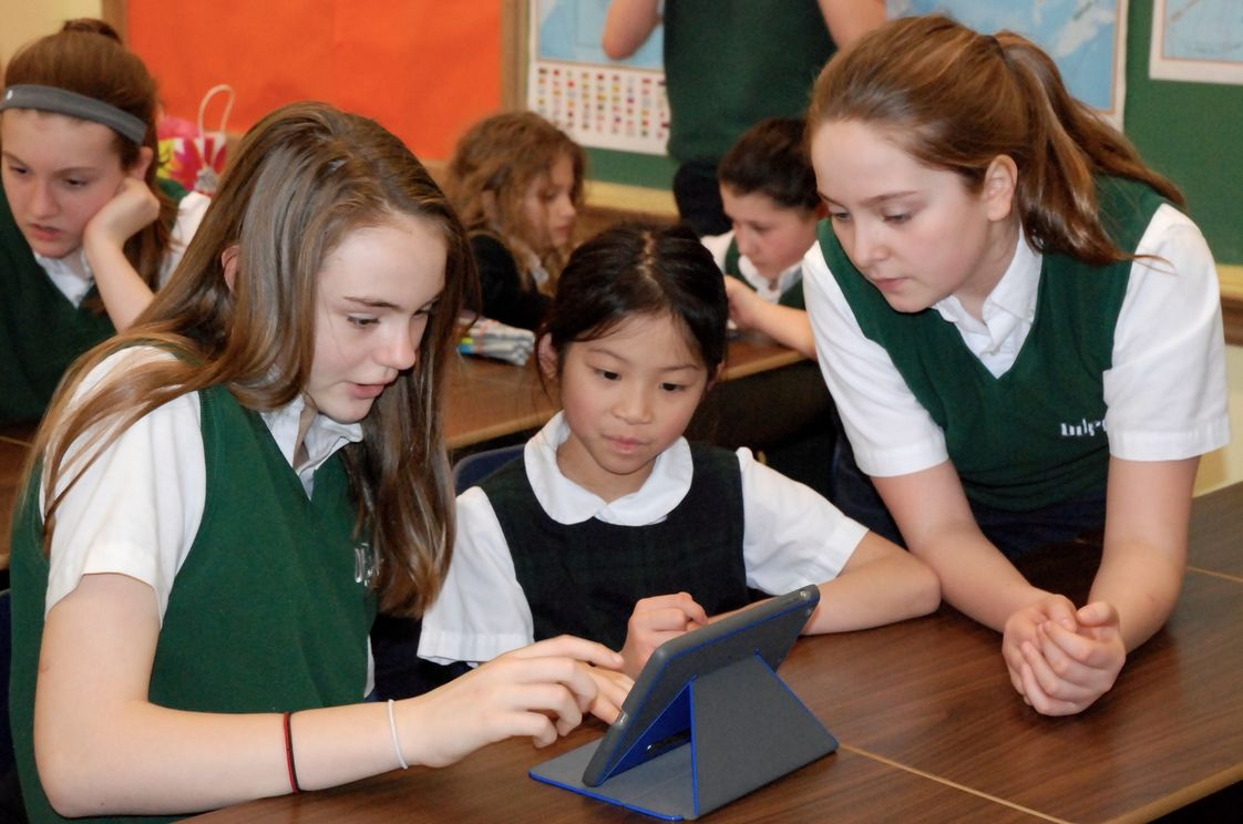 Our Lady Of Perpetual Help Photo #1 - Our 7th grade and 1st grade buddies work on a project together with iPads.